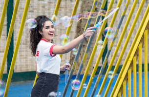 Enthusiastic young woman in playground making bubbles with bubble wandの写真素材 [FYI03598813]
