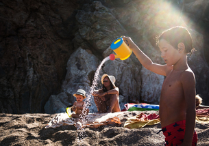 Boy on beach sprinkling toy watering can, Begur, Catalonia, Spainの写真素材 [FYI03598840]