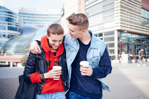 Romantic young couple with takeaway coffee walking together in cityの写真素材 [FYI03598858]