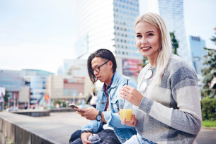 Young couple with takeaway juice and smartphone sitting on wall in cityの写真素材 [FYI03598861]