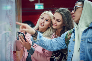 Three young adult friends pointing at map in underground stationの写真素材 [FYI03598901]