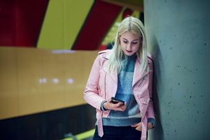 Young woman waiting in underground station looking at smartphoneの写真素材 [FYI03598902]