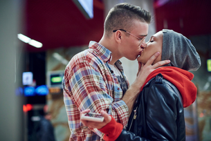 Romantic young couple kissing in underground stationの写真素材 [FYI03598903]