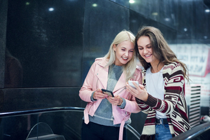 Two young women moving up underground station escalator  looking at smartphoneの写真素材 [FYI03598906]