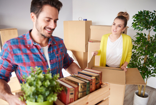 Young couple moving home, packing belongings into cardboard boxesの写真素材 [FYI03598917]