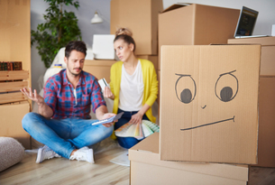 Young couple at home, surrounded by cardboard boxes, working out financesの写真素材 [FYI03598924]