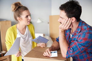 Young couple at home, surrounded by cardboard boxes, working out financesの写真素材 [FYI03598925]