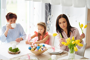 Woman with daughter and mother arranging yellow tulips at easter dining tableの写真素材 [FYI03598942]