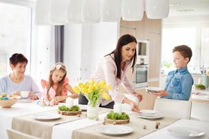 Woman and family preparing place settings at easter dining tableの写真素材 [FYI03598945]