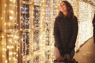 Woman by curtain of fairy lights smiling, Odessa, Odessa Oblast, Ukraine, Europeの写真素材 [FYI03598999]