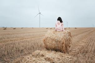 Woman in raincoat on hay bale, Odessa, Ukraineの写真素材 [FYI03599024]