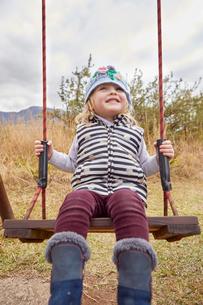 Girl sitting on swing in rural settingの写真素材 [FYI03599038]