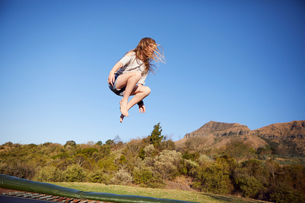 Young girl jumping on trampoline, mid air, in rural settingの写真素材 [FYI03599041]