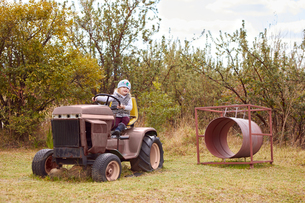 Young girl sitting on tractor, in rural settingの写真素材 [FYI03599042]