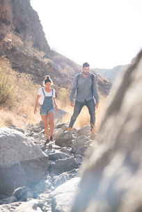 Young hiking couple hiking over rocks in valley, Las Palmas, Canary Islands, Spainの写真素材 [FYI03599168]