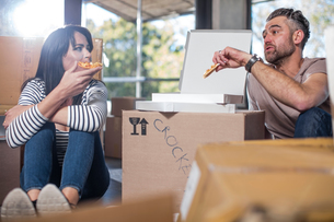 Couple in new home, surrounded by boxes, eating pizzaの写真素材 [FYI03599194]