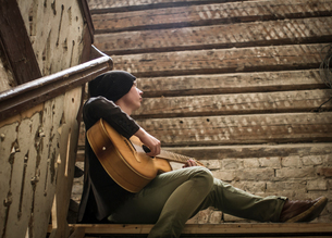 Young man sitting on stairs, playing guitarの写真素材 [FYI03599280]