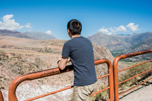 Man leaning against railing, looking at views from above Maras Salt mines, Cusco, Peru, South Americの写真素材 [FYI03599302]