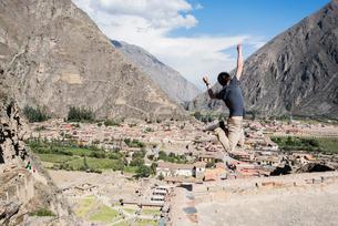 Man Jumping at the top of Ollantaytambo Ruins, Cusco, Peru, South Americaの写真素材 [FYI03599309]