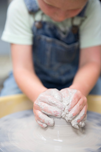 Boy shaping clay on potter's wheelの写真素材 [FYI03599333]