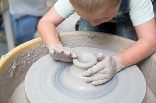 Boy shaping clay on potter's wheelの写真素材 [FYI03599335]