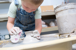 Boy shaping clay on potter's wheelの写真素材 [FYI03599337]
