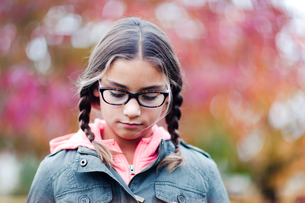 Portrait of girl with plaits and glasses looking downの写真素材 [FYI03599347]