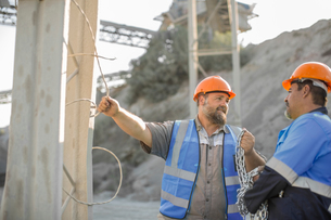 Two quarry workers in quarry, having discussionの写真素材 [FYI03599430]