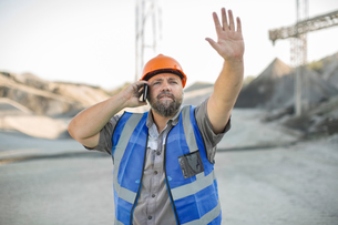 Quarry worker in quarry, using smartphone, gesturing with handの写真素材 [FYI03599434]