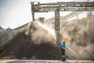 Quarry worker standing beside pile of aggregate in quarryの写真素材 [FYI03599441]