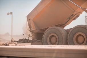 Dump truck in quarry, tipping load of stonesの写真素材 [FYI03599444]
