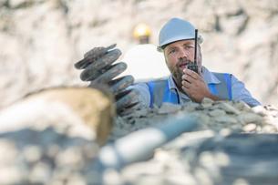 Quarry worker in quarry, talking on walkie talkieの写真素材 [FYI03599446]