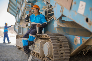 Quarry worker resting on heavy machinery, drinking from flask cupの写真素材 [FYI03599454]