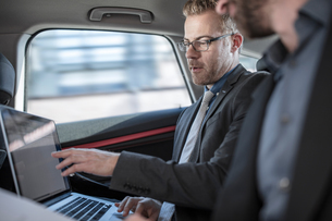 Two businessmen sitting in back of car, looking at laptop screenの写真素材 [FYI03599464]