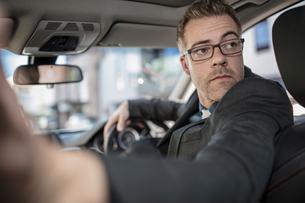 Businessman driving car, looking over shoulder, reversingの写真素材 [FYI03599473]