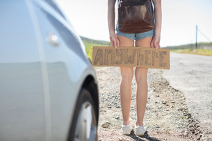 Young woman standing beside car, holding hitch-hiking sign saying 'anywhere', low sectionの写真素材 [FYI03599496]