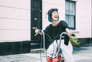 Young stylish woman cycling retro bicycle on streetの写真素材 [FYI03599733]