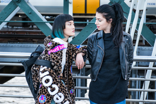 Two young stylish women leaning against handrail on millennium footbridge, London, UKの写真素材 [FYI03599756]