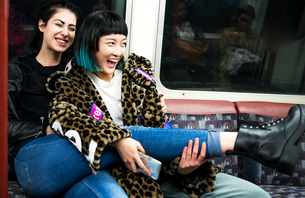 Two young stylish women laughing on underground train carriageの写真素材 [FYI03599765]