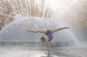 Teenage girl beside fountain, balancing on hands in yoga positionの写真素材 [FYI03599784]