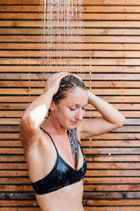 Young woman using outdoor showerの写真素材 [FYI03599785]
