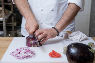 Cropped view of chef slicing red onionの写真素材 [FYI03599807]