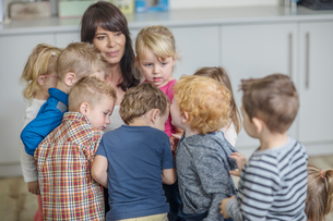 Teacher in classroom, surrounded by young childrenの写真素材 [FYI03599853]