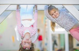 Girls at preschool, portrait climbing and upside down on climbing frame in gardenの写真素材 [FYI03599899]