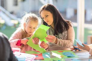 Mid adult woman helping young girl with crafting activityの写真素材 [FYI03599953]