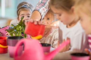 Woman helping young children with gardening activityの写真素材 [FYI03599954]