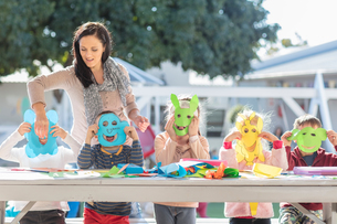 Mid adult woman helping children with crafting activity, children wearing paper masksの写真素材 [FYI03599966]