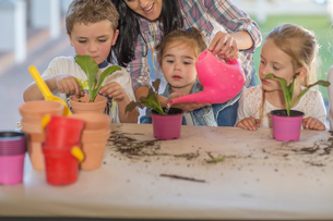 Mid adult woman helping young children with gardening activityの写真素材 [FYI03599974]