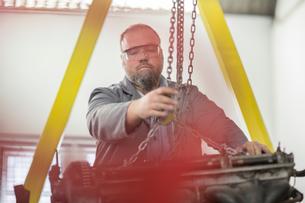 Male car mechanic attaching hoist chain to car engine in repair garageの写真素材 [FYI03600021]