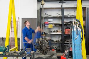 Male car mechanic hoisting car engine in repair garageの写真素材 [FYI03600022]